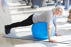 Lächelndes motiviertes Frauentraining mit Sitzball Stockfoto