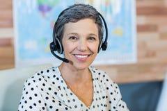 Lächelndes Reisebüro, das an ihrem Schreibtisch sitzt Lizenzfreie Stockfotos