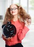 Lächelndes schönes Mädchen mit einer großen Uhr im Büro Stockbilder