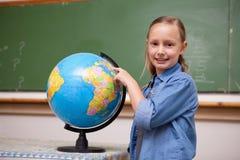 Lächelndes Schulmädchen, das eine Kugel betrachtet Stockbilder
