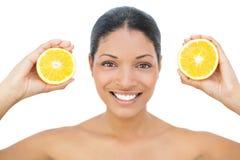 Lächelndes schwarzes behaartes Modell, das orange Scheiben hält Stockbild