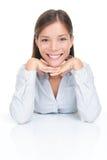 Lächelndes Sitzen der jungen Frau am Tisch Stockfoto
