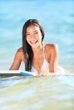 Lächelndes Spielen der Surfbrettfrau im Ozean Stockfotos
