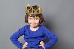 Lächelndes verdorbenes Kind mit goldener Krone an Stockfotos