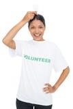 Lächelndes vorbildliches tragendes freiwilliges T-Shirt, das Glühlampe oben hält Lizenzfreie Stockfotografie