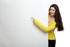 Lächelnfrau, die ihren Finger auf Brett zeigend steht Stockfoto