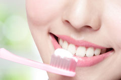 Lächelnfrauen-Bürstenzähne Stockfoto