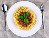 Läcker spagetti bolognese med basilika på den vita plattan Arkivbilder