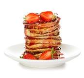 Läckra pannkakor med jordgubben som isoleras på vit Arkivfoto