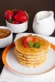 Läckra pannkakor med nya jordgubbar på en platta Royaltyfria Foton