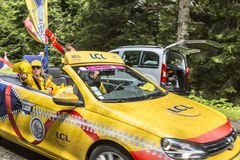 LCL Car During Publicity Caravan. Col de Platzerwasel, France - July 14, 2014: Young woman throwing out promotion yellow caps from a car during the Publicity Royalty Free Stock Images