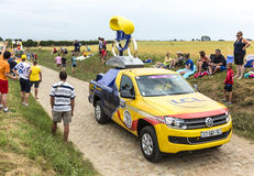 LCL Vehicle on a Cobblestone Road- Tour de France 2015. Quievy,France - July 07, 2015: LCL vehicle during the passing of the Publicity Caravan on a cobblestoned Royalty Free Stock Photography