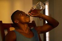Álcool bebendo do homem negro desempregado desesperado em casa apenas Imagem de Stock Royalty Free
