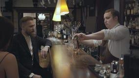 ?lcool de derramamento do barman gordo no vidro usando o copo de medi??o e doa??o dele ao cliente O homem farpado novo e filme