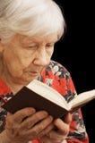 ?ld de hogere vrouw leest het boek stock foto's