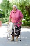 Lderly-Frau, die mit ihrem Wanderer steht Lizenzfreie Stockfotos