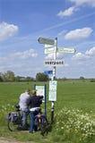 Äldre cyklister som läser färdplanen i bygd Arkivbilder