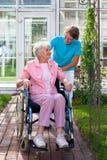 Äldre dam i en rullstol med hennes vårdare Royaltyfri Bild
