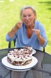 Äldre dam som tycker om en skiva av kakan Royaltyfri Bild