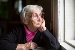 Äldre kvinna i exponeringsglas som hänsynsfullt ut ser fönstret ensamhet Royaltyfria Bilder