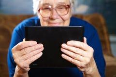 Äldre kvinna med minnestavladatoren Fotografering för Bildbyråer
