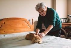 Äldre kvinna som daltar hennes katt på sängen Arkivbilder