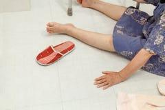 Äldre kvinna som faller i badrum Arkivfoto