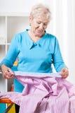 Äldre kvinna som förbereder skjortan till att stryka Royaltyfri Bild