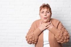 ?ldre kvinna som hostar n?ra tegelstenv?ggen royaltyfri foto