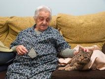 Äldre kvinna som slår hennes katt Arkivbild