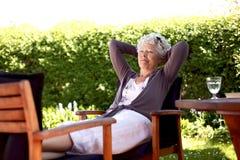Äldre kvinna som vilar i trädgårdträdgård Arkivfoto