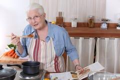 Äldre kvinnamatlagningmatställe Arkivfoton