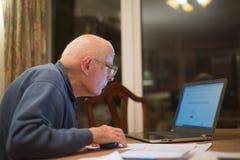 ?ldre man som anv?nder en b?rbar datordator som kontrollerar hans aktieportf?ljer, Hampshire, England, U K royaltyfri bild