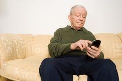 Äldre man som använder fjärrkontroll Fotografering för Bildbyråer