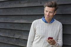 Åldrig man för lycklig mitt som använder den mobila mobiltelefonen Royaltyfri Bild
