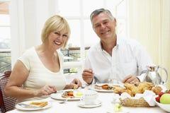 åldriga frukostpar som tycker om hotellmitten Royaltyfri Fotografi