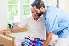 Åldringen att bry sig sjuksköterskaportionpensionären från hjulstol för att bädda ned Royaltyfri Bild