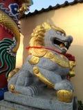 Leão de pedra chinês com pintura do ouro foto de stock