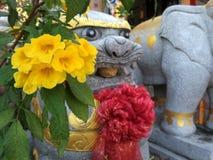 Leão de pedra chinês e flores amarelas vermelhas foto de stock royalty free