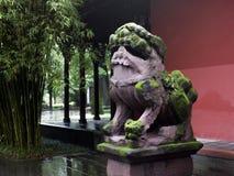 Leão de pedra musgoso na frente de uma construção chinesa foto de stock