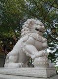 Leão de pedra que joga com a bola de vidro no jardim imagens de stock