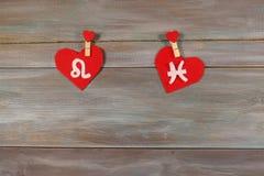 Leão e peixes sinais do zodíaco e do coração Fundo de madeira foto de stock