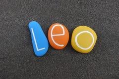 Leão, nome dado masculino composto com as pedras coloridas sobre a areia vulcânica preta imagem de stock