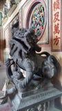 Leão velho de Bronz o guardião de um santuário chinês na comunidade de Tarad Noi no lado do rio de Chaopraya em Banguecoque imagem de stock