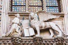 Leão voado e um padre Detail do palácio Palazzo Ducale do ` s do doge em Veneza, Itália imagens de stock
