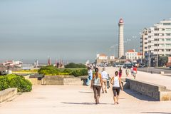 View of the beach of Leca da Palmeira, with people doing exercise and walking, busy street next to the beach, lighthouse in the royalty free stock photography