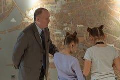 Leçon de géographie à deux filles carte interactif Un maître d'école plus âgé explique une leçon de géographie à deux filles cart images stock