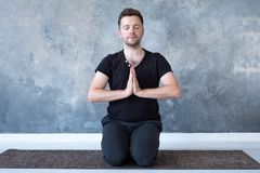 Leçon de pratique de yoga de jeune homme sportif se reposant dans la pose de vajrasana images stock