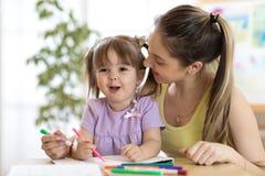 Leçons de dessin de fille d'institutrice gardienne et d'enfant à l'école Photographie stock