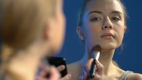 Le?ons visuelles de observation de maquillage d'adolescent f?minin sur le smartphone, appliquant la poudre banque de vidéos
